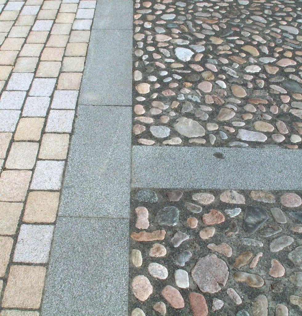 Pigstensbelægning. bord af granit fliser og brostens belægning