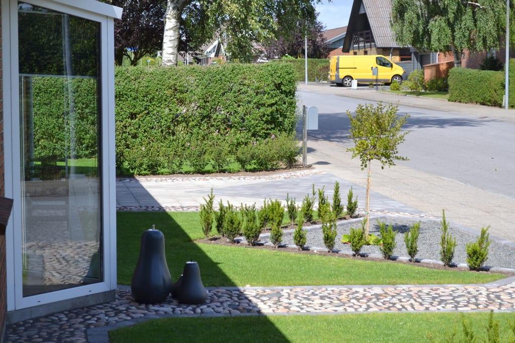 Pigstensbelægning og græsplæne i forhave