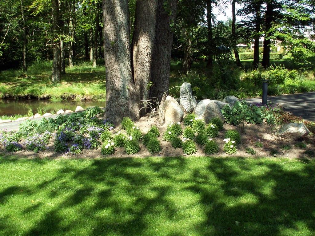 Forhøjet bed med beplantning og pyntesten i granit