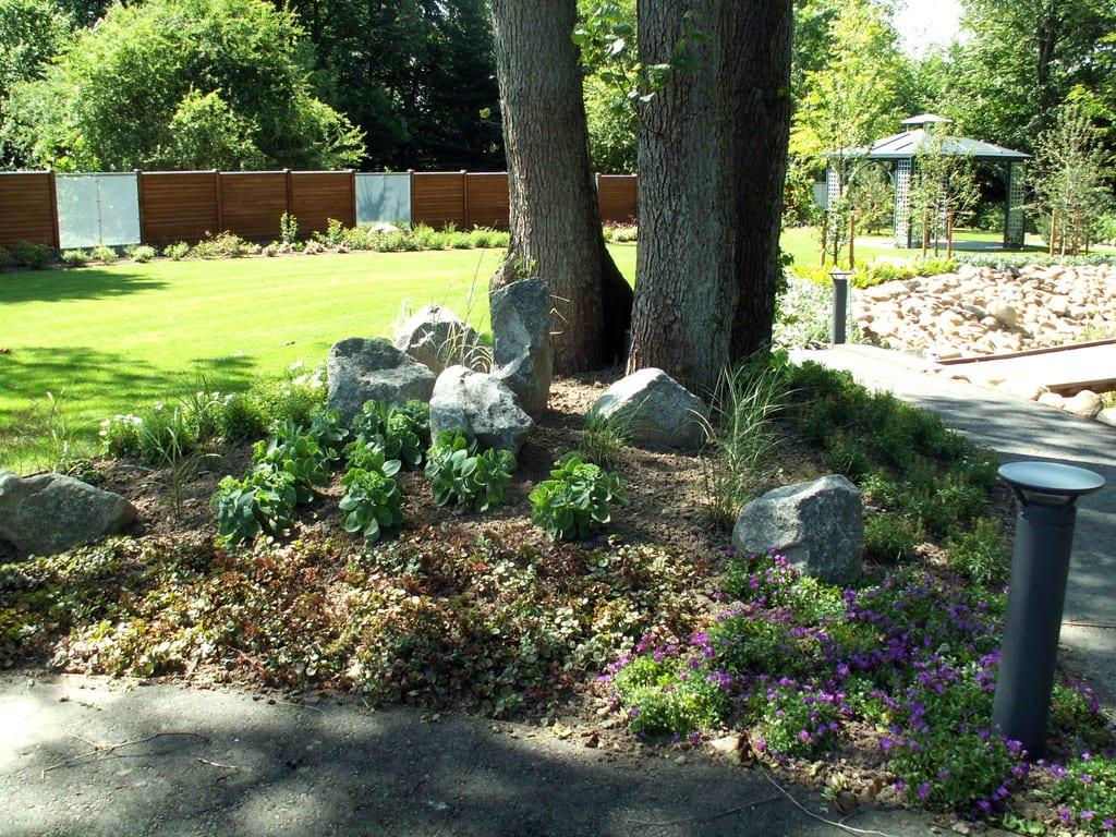Bed med beplantning og granit pyntesten