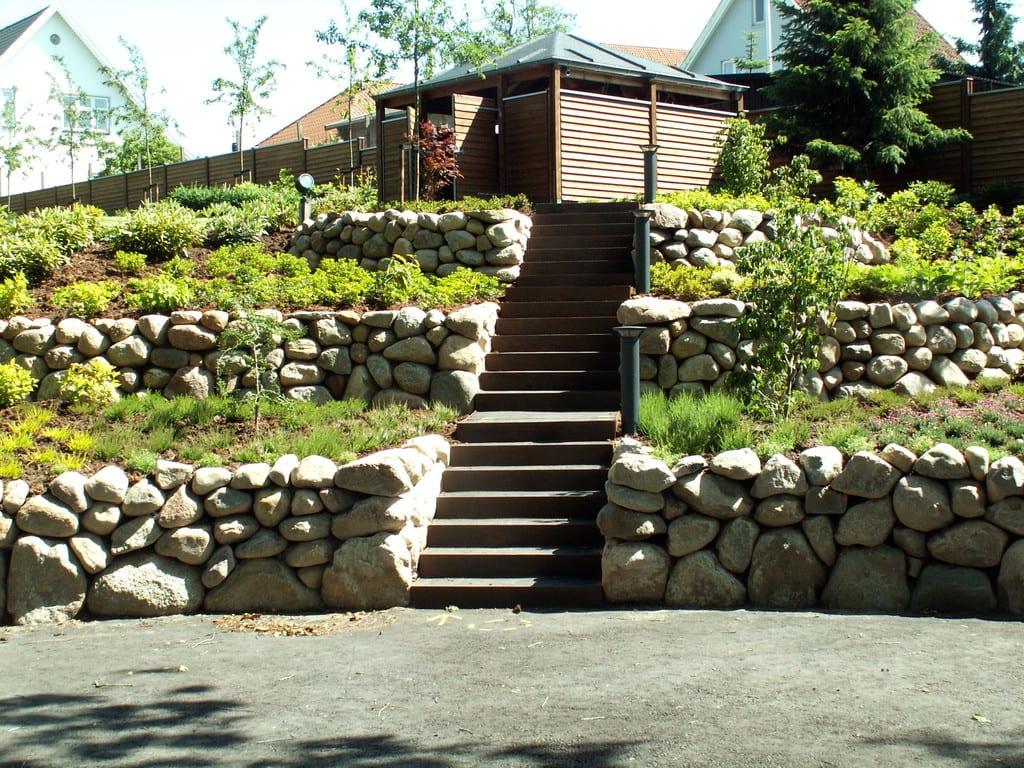 Kampestens støttemur i niveauer langs trappe i corten trin