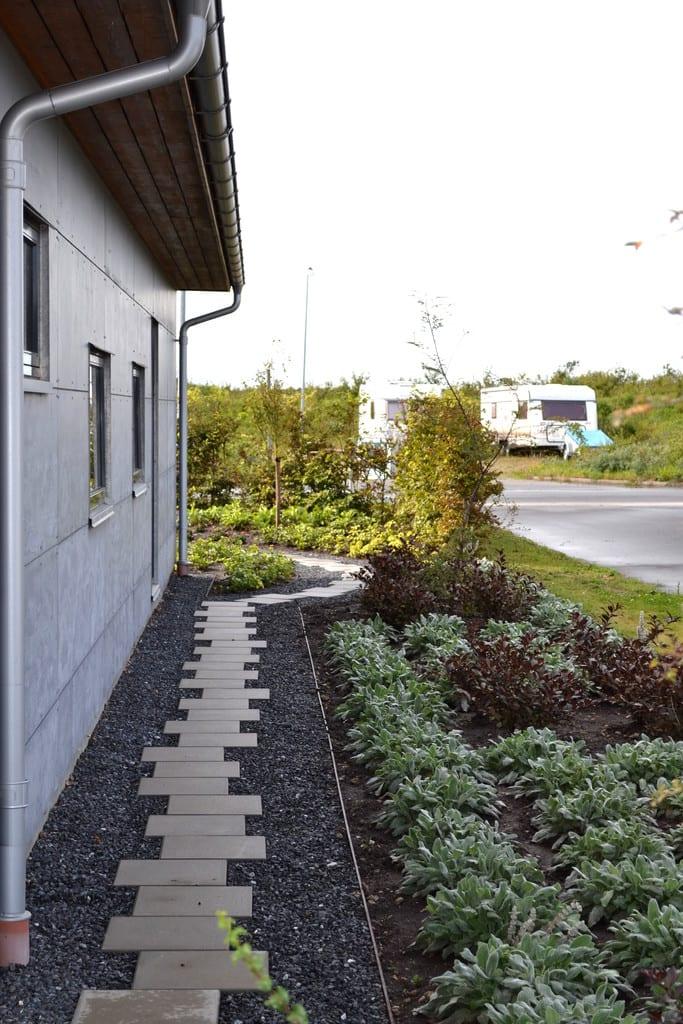 Beton fliser forskudt og granit skærver afgrænses af beplantning med jernkant