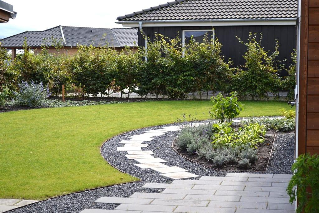 Græsplæne, sti og plantning afgrænses af jernkant