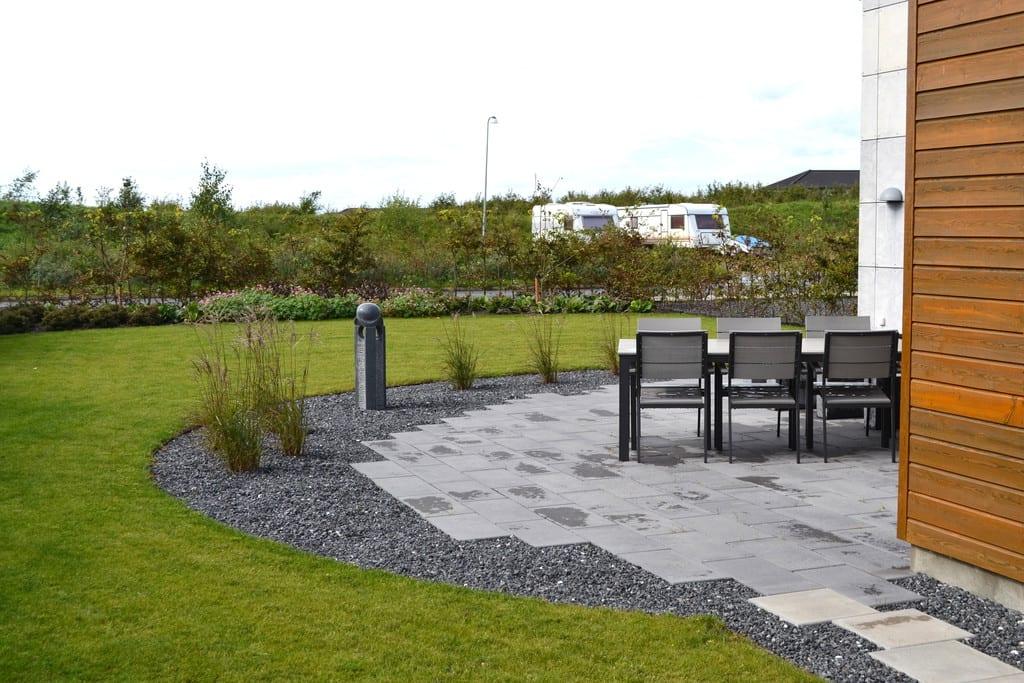 Halvcirkel med beton fliser, granit skærver og prydgræsser